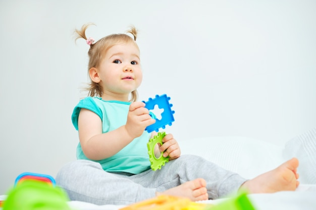 Маленькая девочка играет с красочными игрушками