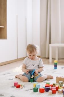 아이 방 바닥에 다채로운 나무 벽돌을 가지고 노는 어린 소녀