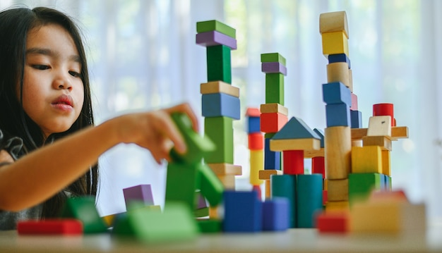 Little girl  playing with construction toy blocks building a tower