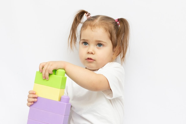 Little girl playing with cubes on white background