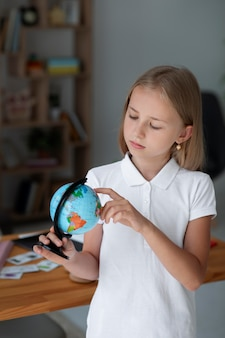 Little girl playing with an earth globe