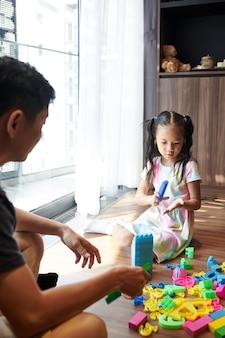 집에서 아버지와 놀고 플라스틱 블록으로 타워를 짓는 어린 소녀