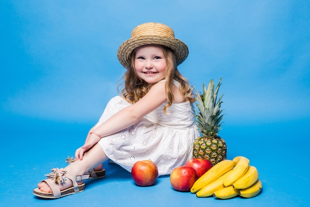 Little girl playing with fruits isolated on a blue wall