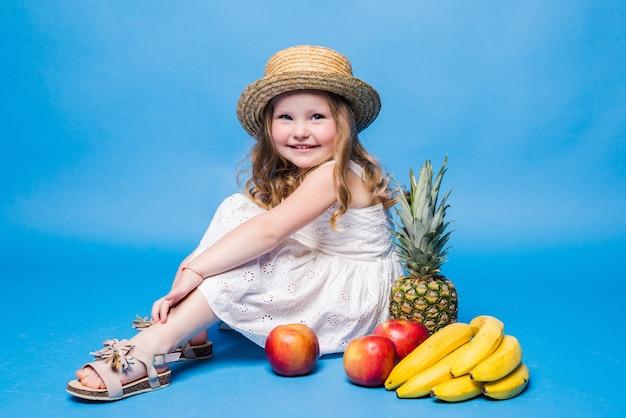 青い壁に分離された果物で遊ぶ少女