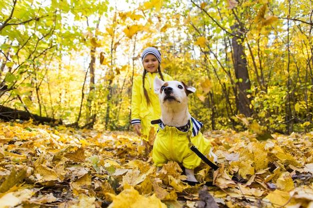 가 숲에서 그녀의 강아지와 함께 재생하는 어린 소녀. 아이와 잭 러셀 테리어 개.