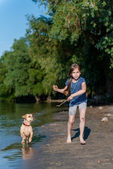 Little girl playing with her dog in the river