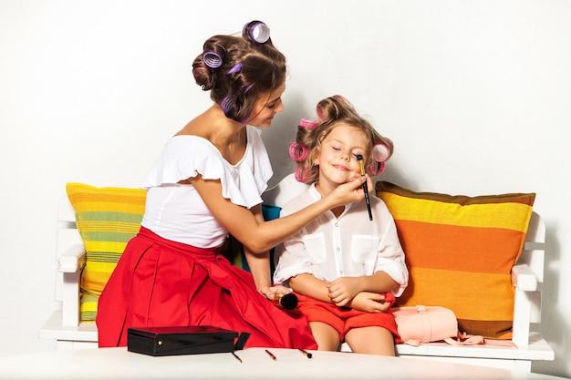 Bambina che gioca con il trucco di sua madre su bianco
