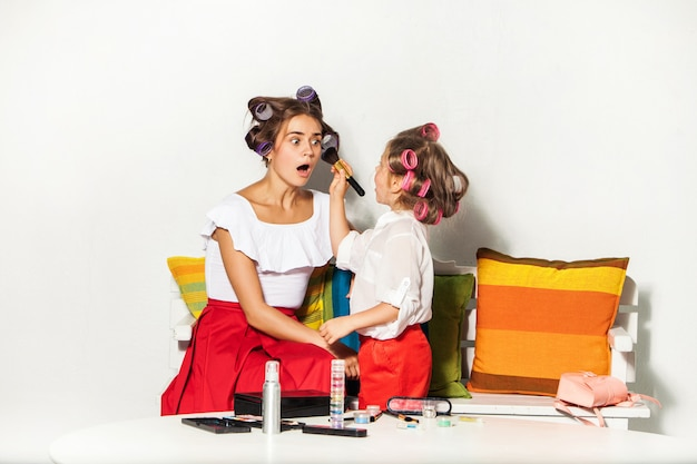 Маленькая девочка играет с маминой косметикой