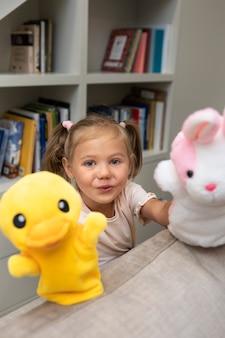 Маленькая девочка играет со своими куклами дома