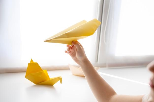 Маленькая девочка играет с бумагой оригами дома