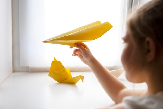 Little girl playing with origami paper at home