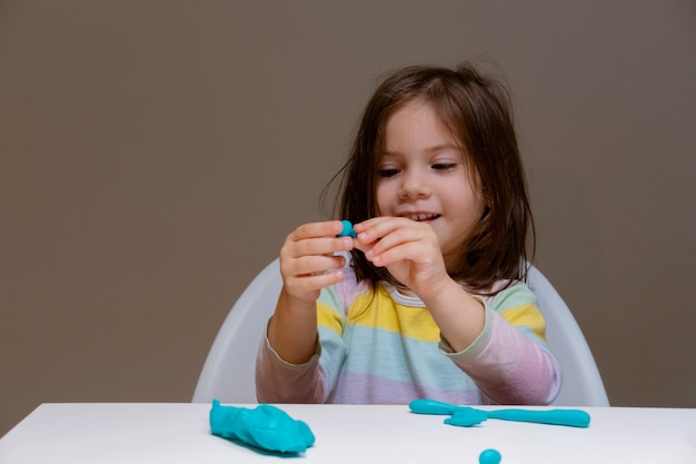 Little girl playing with plastiline (play dough) on gray background.