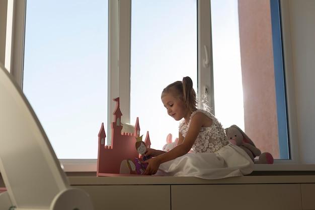 Bambina che gioca con i burattini a casa
