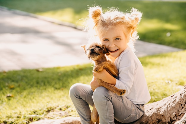 Little girl playing with a puppy outdoors