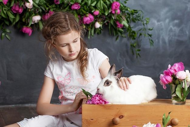 本物のウサギと遊ぶ少女。イースターの子供と白いウサギ。子供やペットが遊ぶ。動物と子供のための楽しさと友情。
