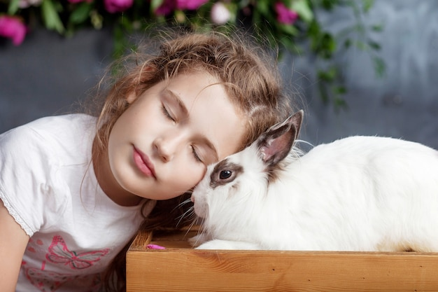 Little girl playing with real rabbit. child and white bunny on easter. kid kiss pet. fun and friendship for animals and children.