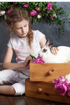 Little girl playing with real rabbit. child and white bunny on easter. kids and pets play. fun and friendship for animals and children.