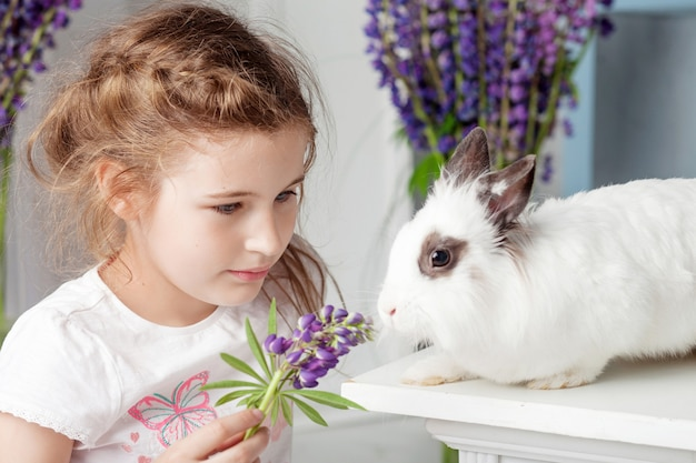 Little girl playing with real rabbit. child and white bunny on easter. toddler kid feeding pet animal. kids and pets play. fun and friendship for animals and children.