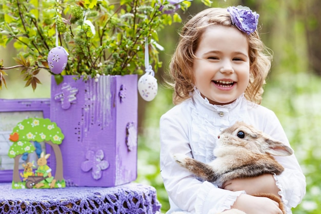 Little girl  playing with real rabbit in the garden. laughing child at easter egg hunt with  pet bunny. spring outdoor fun for kids with pets