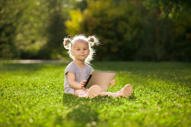 Little girl playing with a tablet in the park