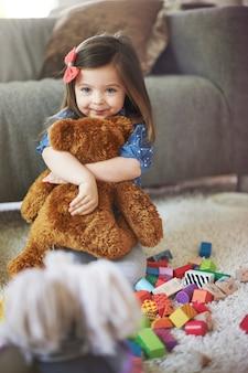 Маленькая девочка играет с игрушками в гостиной