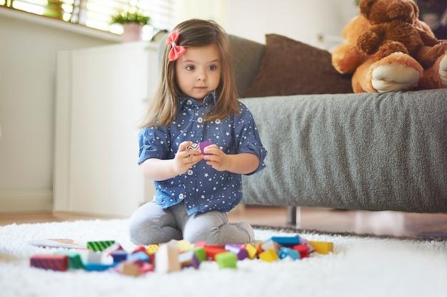 거실에서 장난감을 가지고 노는 어린 소녀