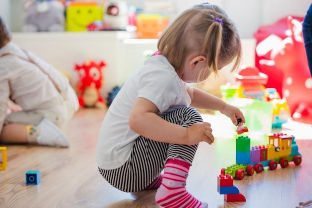 列車のおもちゃで遊んでいる少女