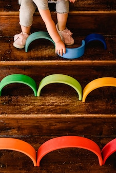 Little girl playing with waldorf montessori rainbow of various colors concentrating