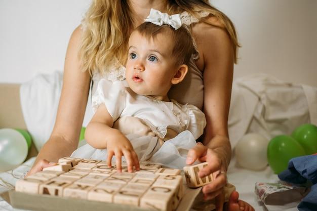 木製のabcで遊ぶ少女は、安全のためにプラスチックフリーの木製のゼロウェイストの子供のおもちゃをブロックします