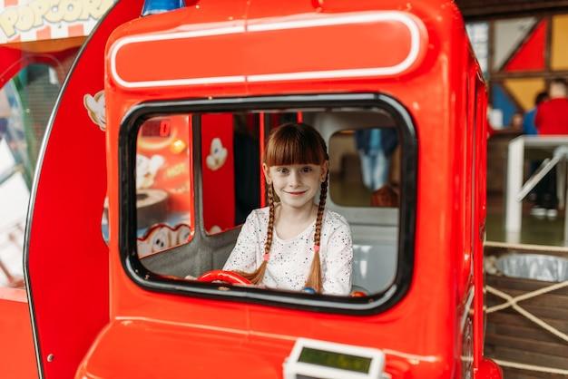 小さな女の子がバスの運転手、ゲーム機を果たしています。