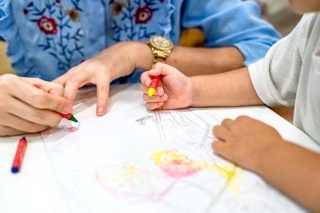 Маленькая девочка играет и учится раскрашивать