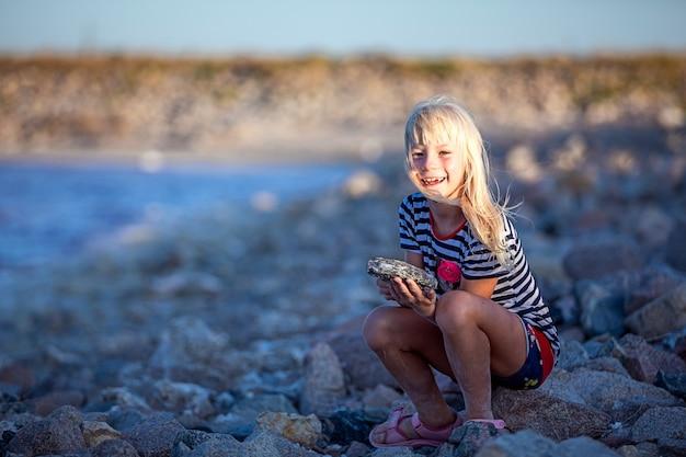 小さな女の子が海岸で遊ぶ