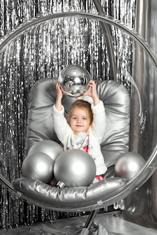 Little girl plays in a chair a glass bowl with silver balls. snow queen cover