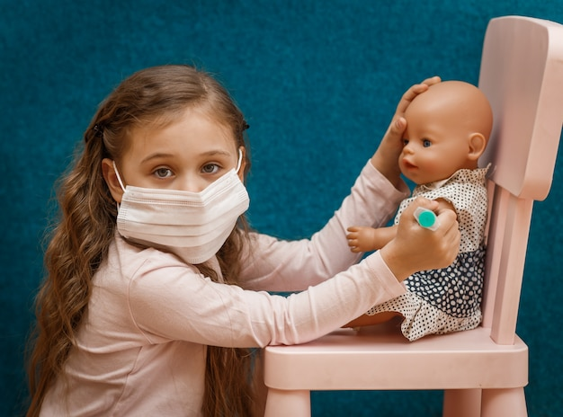 Little girl plays doctor, makes an injection to the doll