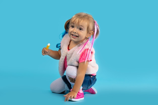 Little girl plays on the floor and eats sweets. photo on a blue wall. holiday concept, halloween.