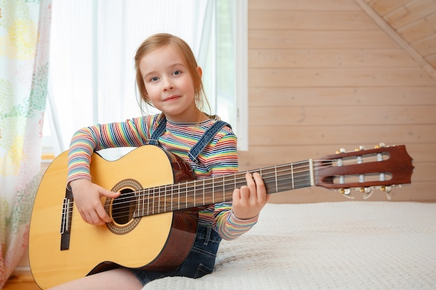 Little girl plays the guitar at home.