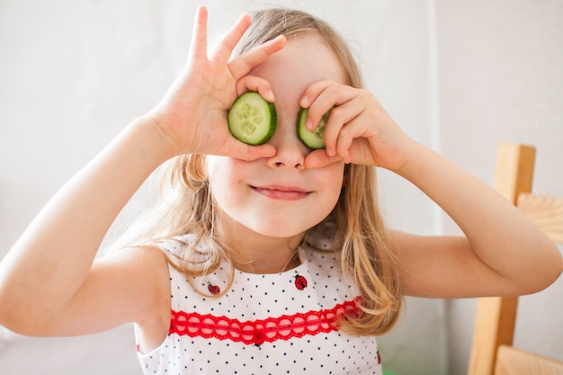 Little girl plays at home, as if making a cucumber face mask