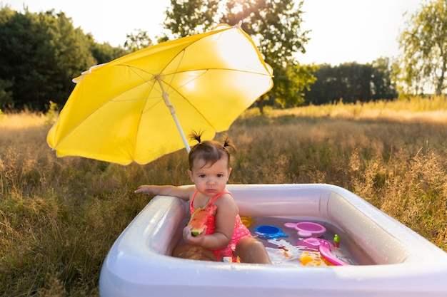 Little girl plays in the inflatable pool.