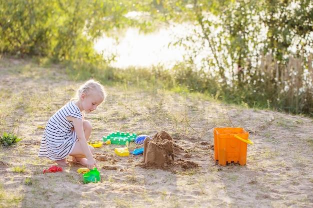 小さな女の子は川のそばでおもちゃで砂の上で遊ぶ