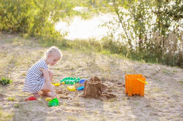 Little girl plays on sand with toys by river