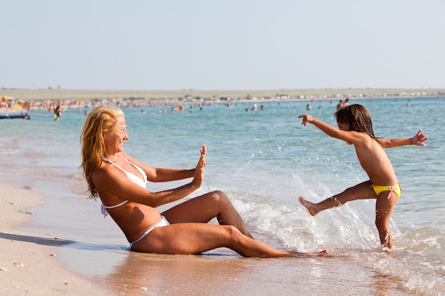 Little girl plays and splashes water on a young blonde in a white bikini