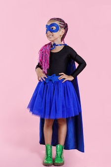 Little girl plays superhero. kid on the space of bright pink wall, wear in colorful clothes green boots, pink hair.