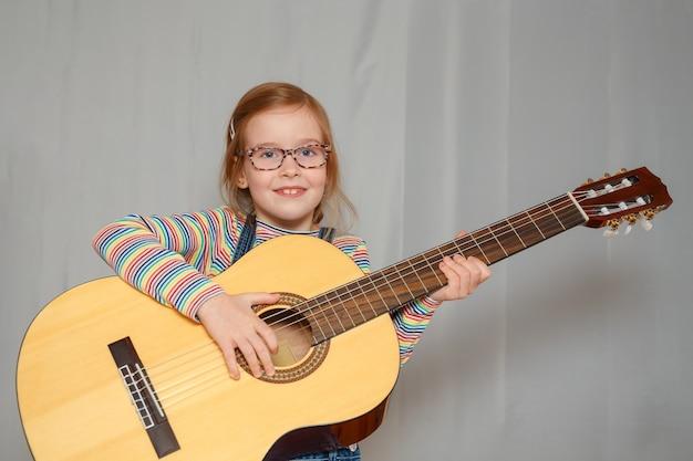 少女は家でギターを弾きます。