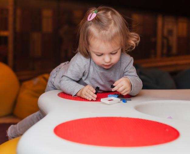 어린 소녀는 어린이 엔터테인먼트 센터의 테이블에서 장난감 벽돌을 재생합니다.