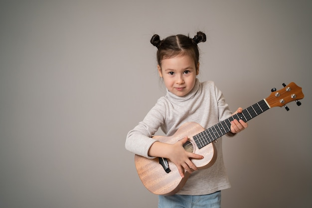 Little girl plays ukulele creative development in children musical education from childhood teaching music online at home