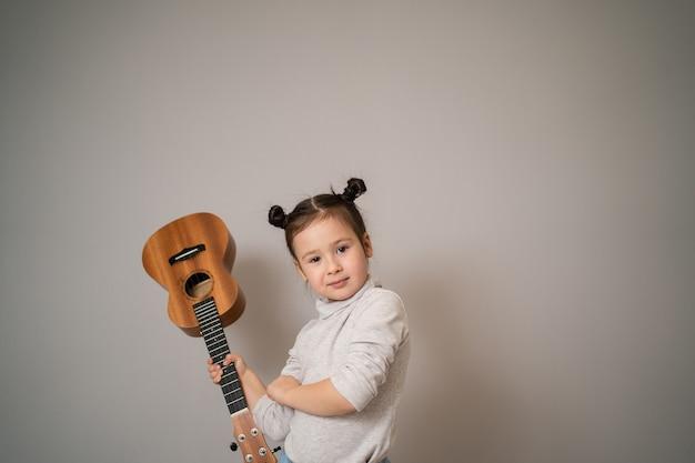 어린 소녀는 우쿨렐레를 재생합니다. 아이들의 창의적인 발달. 어린 시절부터 음악 교육. 집에서 온라인으로 음악을 가르칩니다.