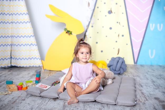 Little girl plays wigwam with colorful toy bricks in childrens room