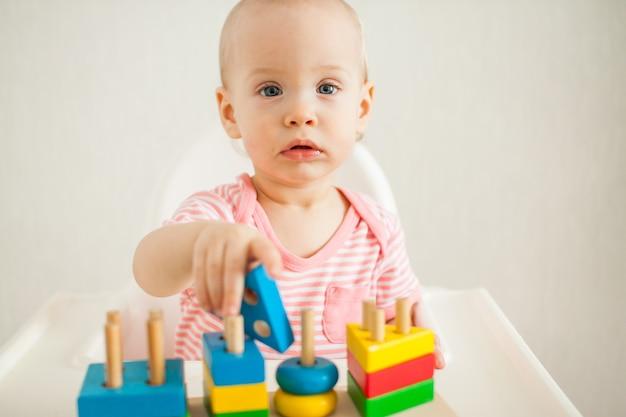 어린 소녀는 교육 장난감-멀티 컬러 나무 피라미드로 재생됩니다. 훌륭한 운동 능력과 논리적 사고의 발달. 고품질 사진