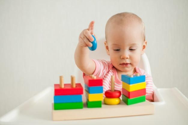 Маленькая девочка играет с развивающей игрушкой - разноцветной деревянной пирамидкой. развитие штрафа