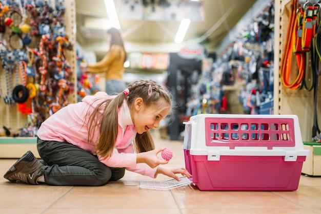 小さな女の子はペットショップで猫のキャリアで遊ぶ